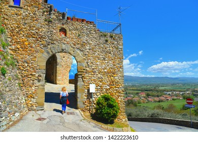 Young woman under Old stone arch gate and narrow street in the medieval village of Anghiari near city of Arezzo with tiber valley in background in Tuscany, Italy