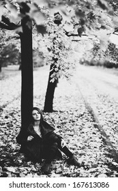 Young woman under tree. Black and white film style colors.