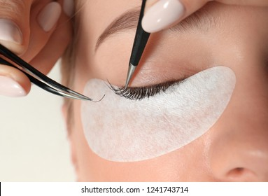 Young woman undergoing eyelash extension procedure, closeup