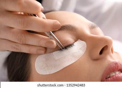 Young woman undergoing eyelash extension procedure in beauty salon, closeup