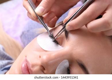 Young woman undergoing eyelash extensions procedure, closeup