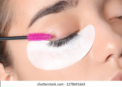 Young woman undergoing eyelashes extensions procedure, closeup