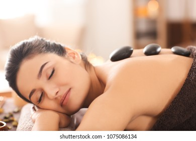 Young woman undergoing hot stone therapy on massage table at spa salon