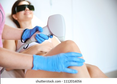 Young woman undergoing laser epilation procedure in beauty salon