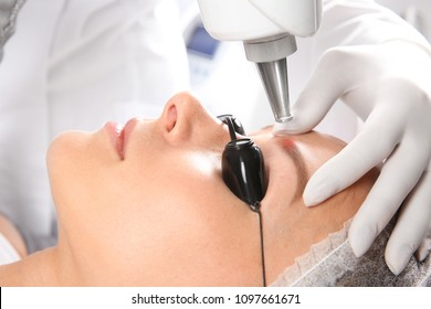 Young woman undergoing laser removal of permanent makeup in salon. Eyebrow correction