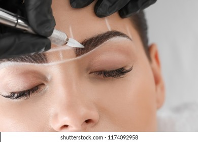 Young woman undergoing procedure of eyebrow permanent makeup in beauty salon, closeup