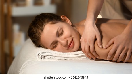 Young woman undergoing procedure of massage in beauty salon