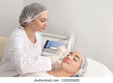 Young woman undergoing procedure of permanent eyebrow makeup in tattoo salon