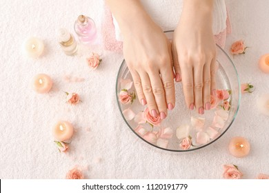 Young woman undergoing spa manicure treatment in beauty salon