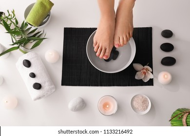 Young woman undergoing spa pedicure treatment in beauty salon