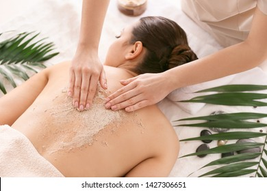 Young woman undergoing treatment with body scrub in spa salon