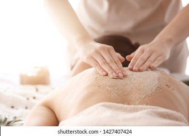 Young woman undergoing treatment with body scrub in spa salon, closeup
