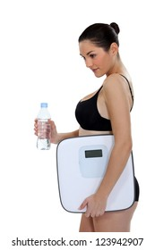 Young woman in underwear holding bottle of water and scales