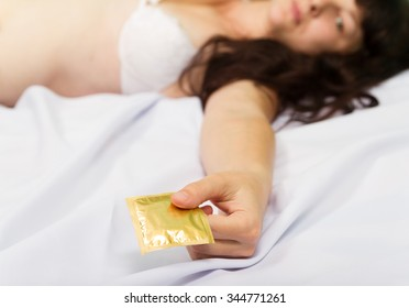 Young woman in underwear on bed shows a condom.