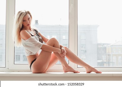 young woman in underwear sitting on windowsill