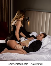 young woman undress a handsame guy on a bed in hotel room
