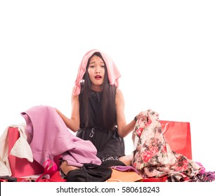 Young woman is unhappiness and sitting on the floor with bags shopping clothes isolated on white in studio