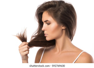 Young woman is unhappy with split ends of her hair