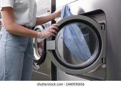 Young woman unloading washing machine in dry-cleaning, closeup