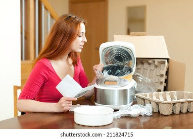 Young woman unpacking and reading user manual for new crock-pot at home