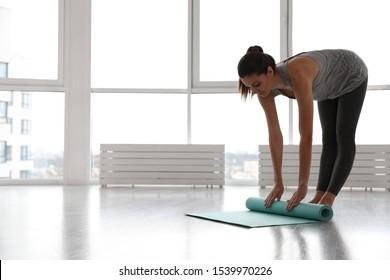 Young woman unrolling mat in yoga studio