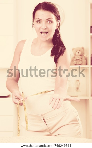 Young woman is upset with measurement of  waist