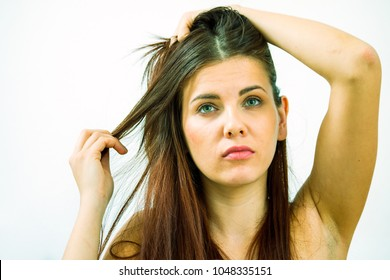 young woman upset with messy hair with dandruff