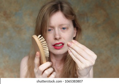 Young woman upsetting looking into the hair that has fallen out while brushing