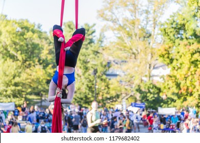 Young woman upside down on a red ribbon is hidding her face