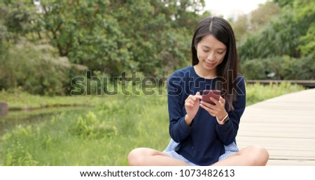 Young woman use of mobile phone in countryside