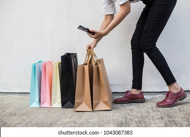 the young woman use smartphone check internet online business after happy holidays shopping with many colorful bags modern lifestyle people in city