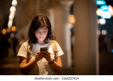 Young woman use smartphone on Macau street at night