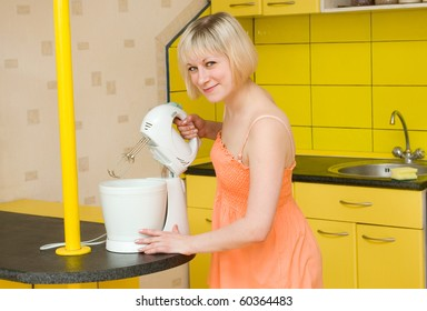 The young woman uses a mixer on kitchen
