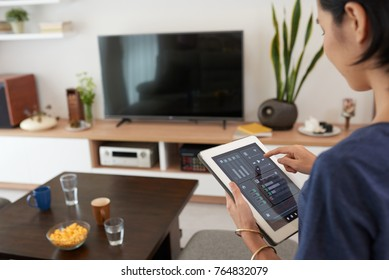 Young woman using application in his smart home
