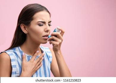 Young woman using asthma inhaler on color background. Space for text
