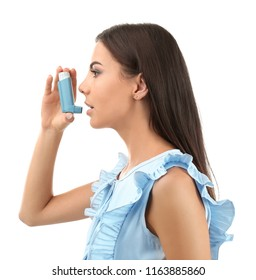 Young woman using asthma inhaler on white background