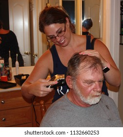 Young woman using barber tool to cut older man's hair