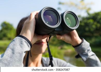 Young woman using binocular for bird watching