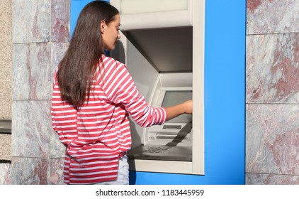Young woman using cash machine outdoors