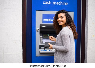 young woman using a cash point