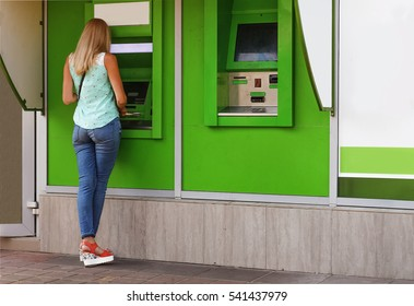 young woman using a cash point. Young girl using ATM