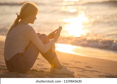 Young woman using a cellphone at the beach during sunset.