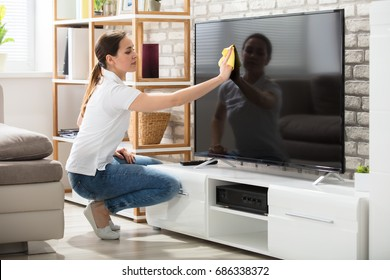 Young Woman Using Cloth To Clean The Television Screen In Living Room