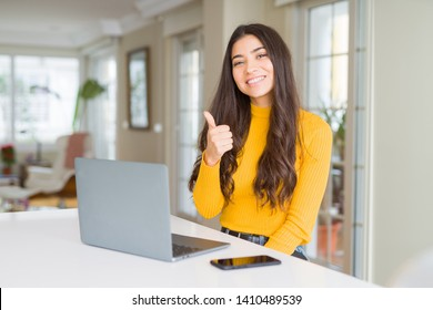 Young woman using computer laptop doing happy thumbs up gesture with hand. Approving expression looking at the camera with showing success.