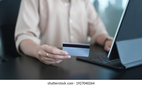 Young woman using computer tablet and holding credit card for shopping online or internet banking on blank office desk.