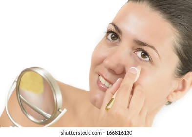 Young woman using concealer looking in the mirror