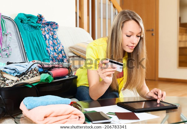 Young woman using credit card and tablet for reserving plane ticket online
