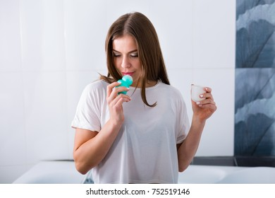 Young woman using deodorant at her bathrooms