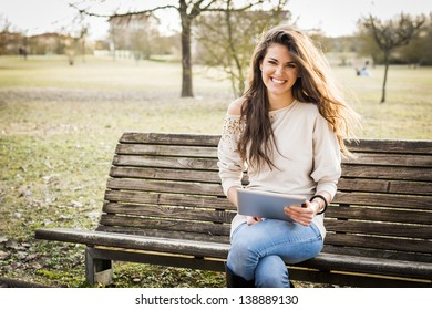 Young woman using digital tablet at the park