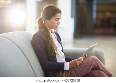 Young woman using digital tablet while sitting on sofa in office